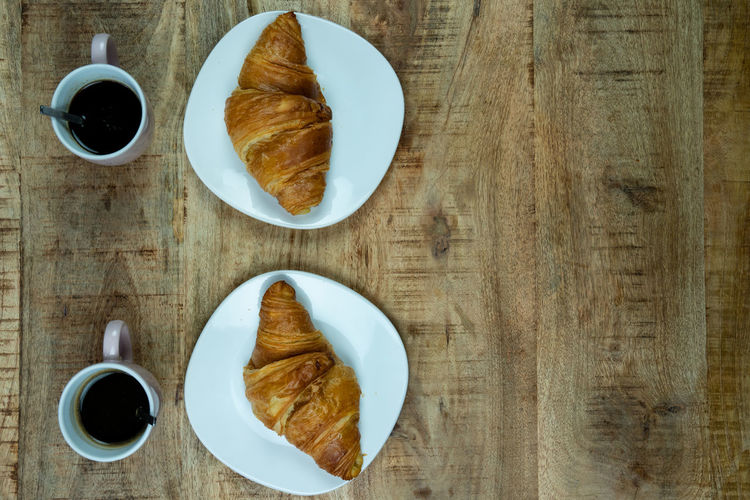 Breakfast or lunch for two. Freshly baked Croissants on a plate with coffee. On a wooden background, top view Food And Drink Coffee Table Cup Coffee - Drink Drink Freshness Coffee Cup Food Directly Above Refreshment Mug Baked Indoors  Plate Breakfast Still Life Croissant Meal Wood - Material French Food No People Baked Pastry Item Crockery Snack Croissants Lunch Espresso Scent Aroma Backgrounds Concept Card Text Copy Space Tasty Eating Vintage Rustic Brown Pastry Close-up