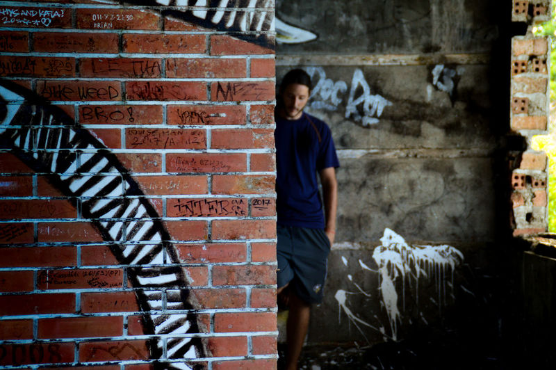 Close-up of graffiti on brick wall with man standing in background