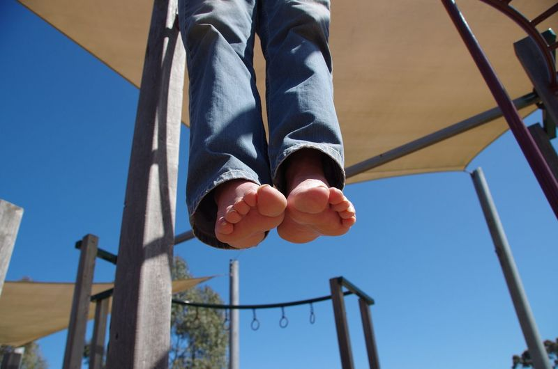 Low section of boy hanging on monkey bars at park