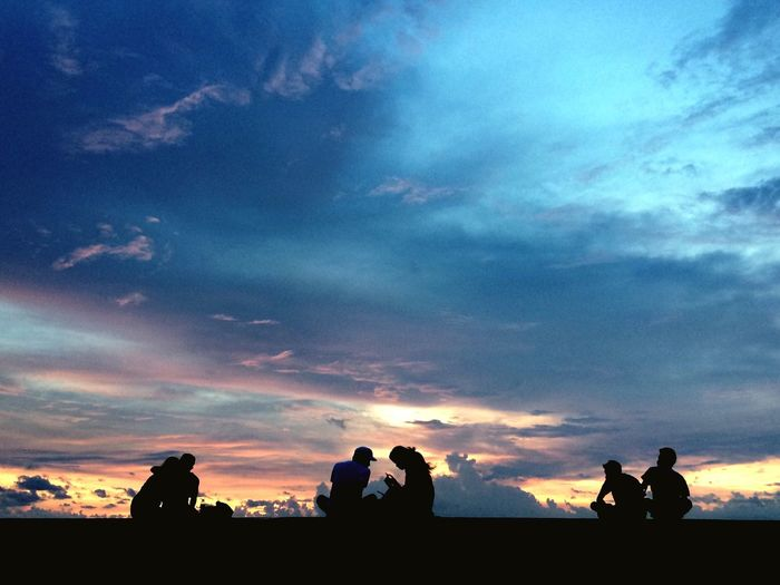 Silhouette people against scenic sky