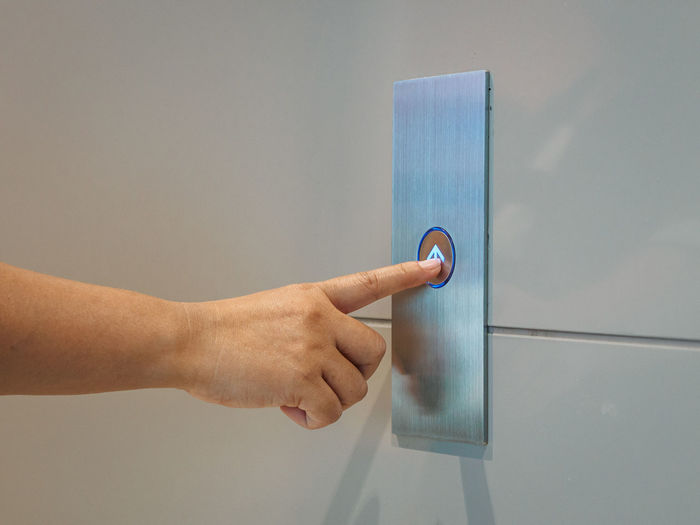 Cropped hand of person pressing elevator button on wall