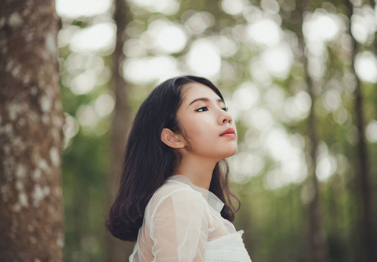 Close-up of young woman standing against tree