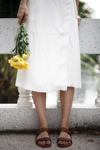 Low section of woman in white dress holding yellow flowers while standing on bridge
