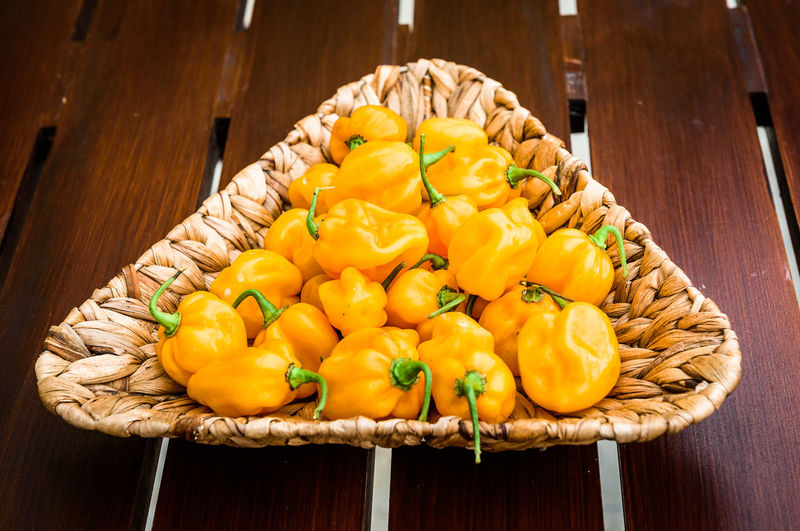 Yellow orange ripe habanero hot chili peppers on a wooden plate from caribbean or mexico. Capsicum Annuum Chili Pepper Hot Pepper Plant Bunch Capsaicin Capsicum Capsicum Chinense Capsicum Pepper Chili  Fruit Group Habanero Habanero Orange Habanero Yellow Homegrown Hot Peppers Isolated White Background Organic Organic Food Pepper Studio Shot Vegetable Yellow
