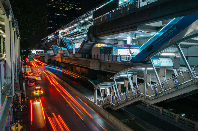 light trails of the backlights of moving cars and skytrain station at night in Bangkok, Thailand Built Structure Architecture Illuminated Building Exterior City Transportation Motion Night Street Long Exposure Blurred Motion Speed Light Trail Mode Of Transportation Road Land Vehicle Traffic High Angle View on the move Bridge - Man Made Structure Outdoors Light Skytrain Bangkok