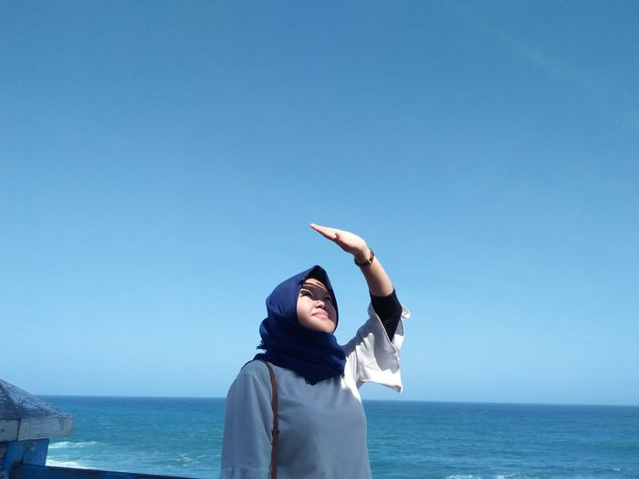 Woman shielding eyes while standing at beach against clear blue sky