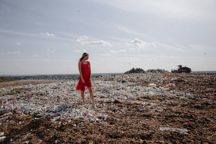 Woman standing amidst garbage against sky