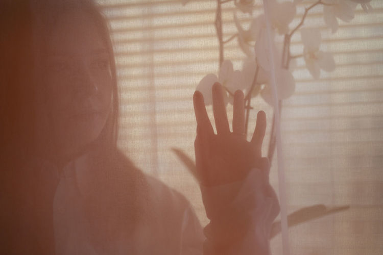 Shadow of woman hand on window at home