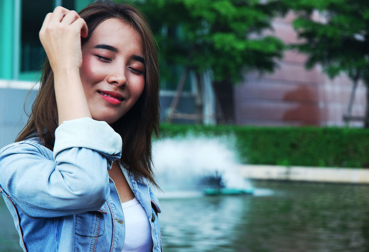 Beautiful Young Woman Wiping Sweat With Tissue Paper Against Fountain