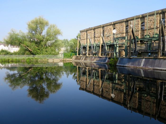 Industrial Building With Reflection On River Against Clear Sky