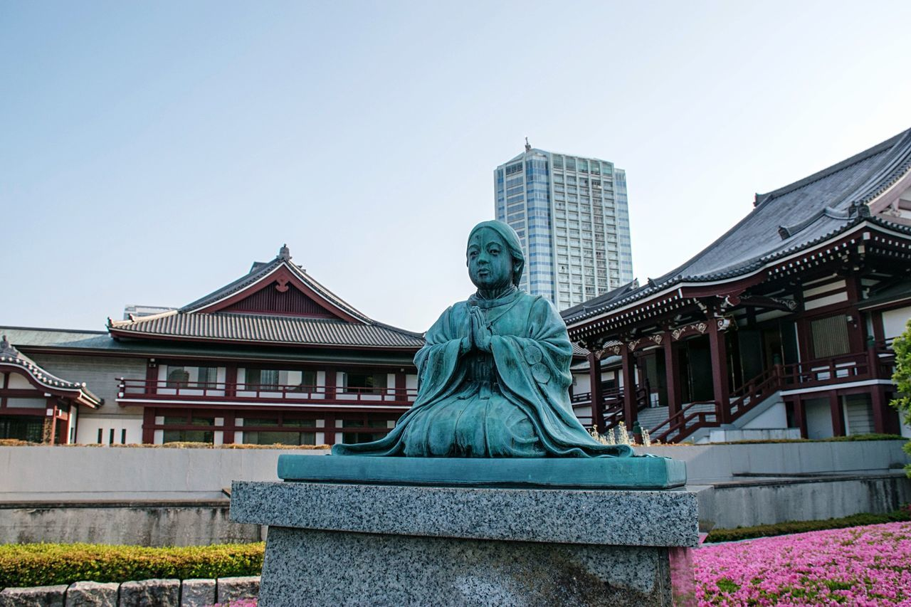 Statue In City Against Clear Sky
