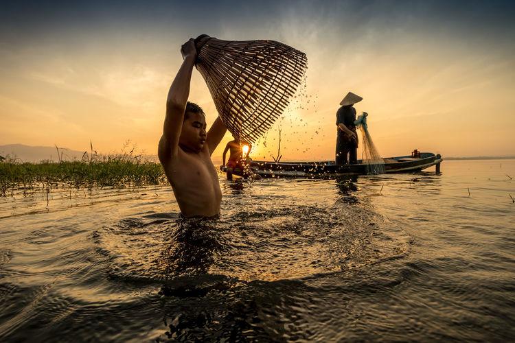Men fishing on beach against sky during sunset