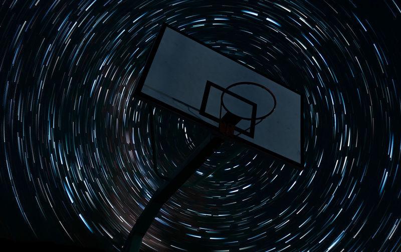 Digital composite image of basketball hoop against light painting in sky