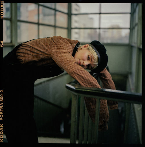 Portrait of teenage girl standing by railing