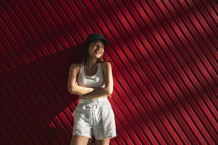 Portrait of smiling young woman standing against red wall