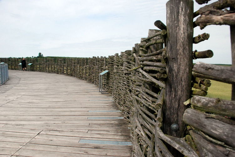 Boardwalk with log fence against sky