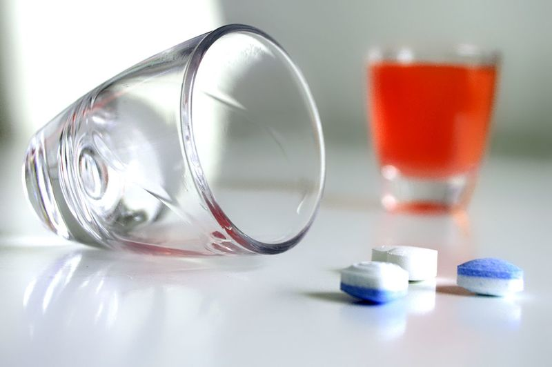 Close-Up Of Drinking Glass By Medicines On Table