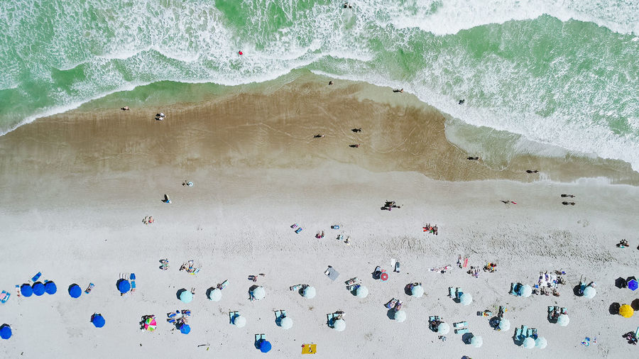 Drone view of a beach in Summertime Summertime Vacations Beach Crowd Day Group Of People High Angle View Holiday Land Large Group Of People Leisure Activity Lifestyles Nature Outdoors Real People Sand Sea Sport Surfing Vacation Water Wave