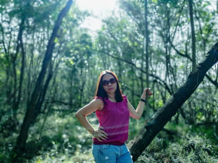 Portrait Of Woman Wearing Sunglasses While Standing In Forest