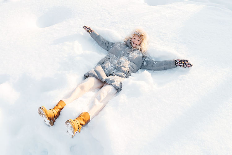 Full length of woman lying down on snow covered land