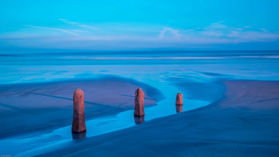 Water Sea Blue Sky Horizon Horizon Over Water Scenics - Nature Beauty In Nature Tranquil Scene Tranquility Nature Cloud - Sky No People Day Idyllic Land Outdoors Post Non-urban Scene Wooden Post Turquoise Colored Seascape Breakwater Sunrise Bluesky