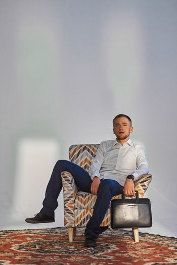 Full length of young man sitting on chair
