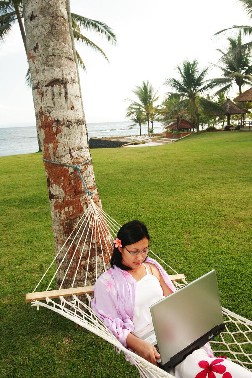 Woman Using Laptop In Hammock