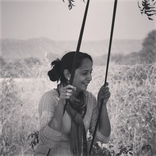 Young woman enjoying rope swing at field