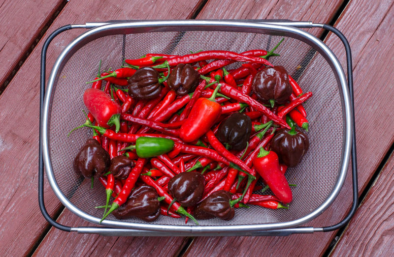 Close-up of red chili peppers in colander on table