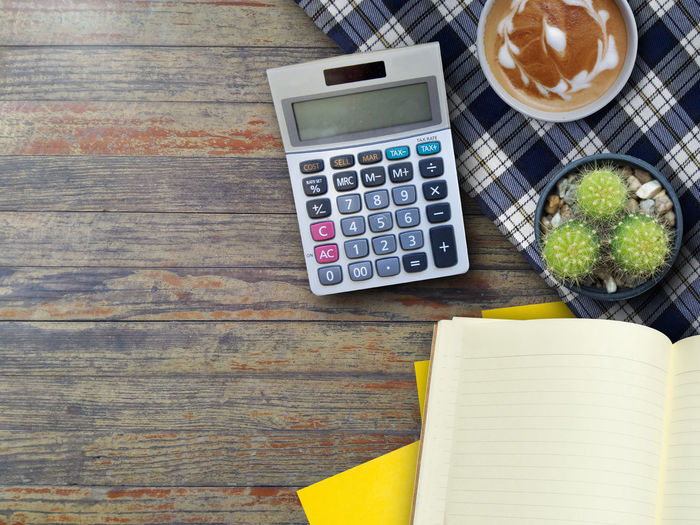 High Angle View Of Book With Calculator And Plant On Wooden Table