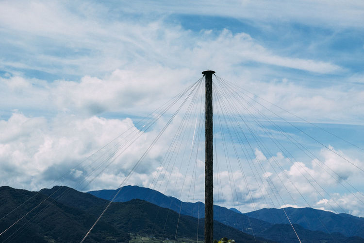 Low Angle View Of Cables Attached To Pole Against Cloudy Sky