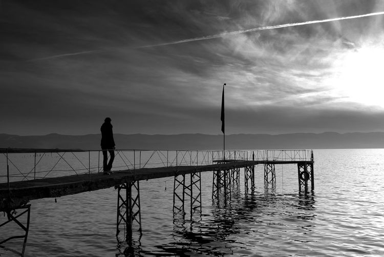 Rear view of woman walking over sea on pier