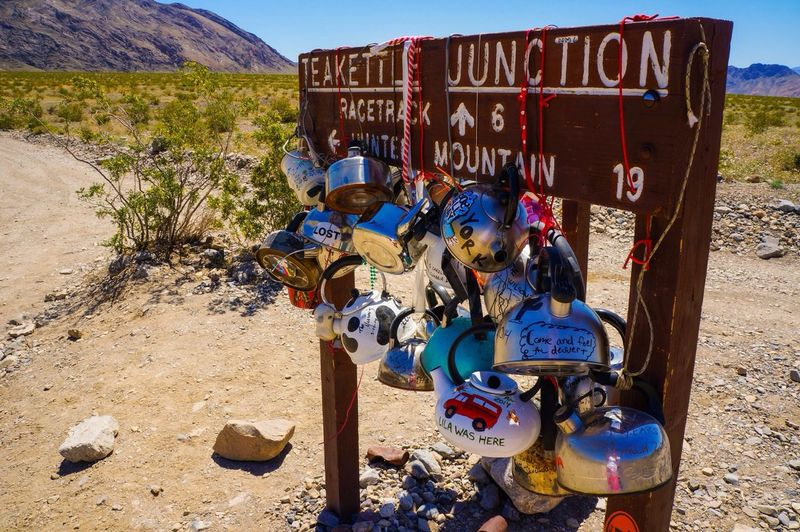 Various tea kettles hanging on signboard at death valley national park