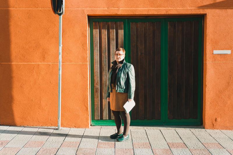 Full length of woman standing against closed door on sunny day