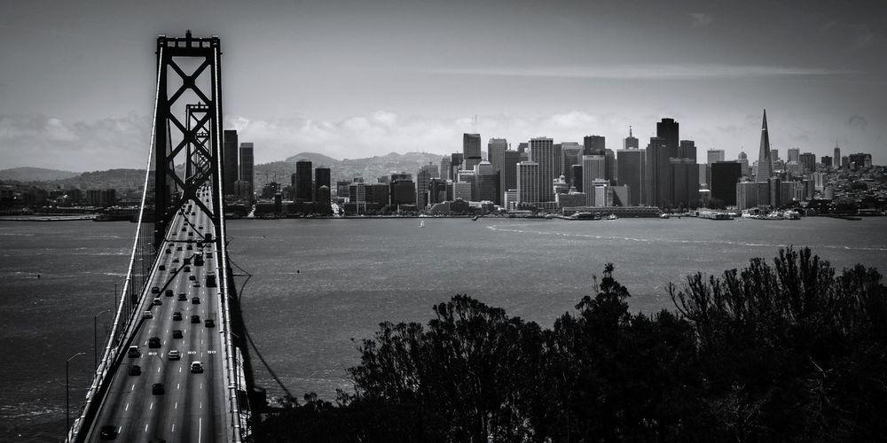 Bay bridge over bay by buildings against sky