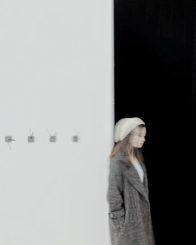 Side view of a young woman standing against the wall