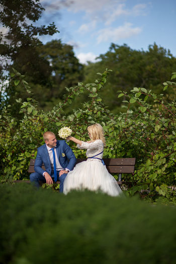 Bridal Couple Sitting On Bench Against Plants At Park