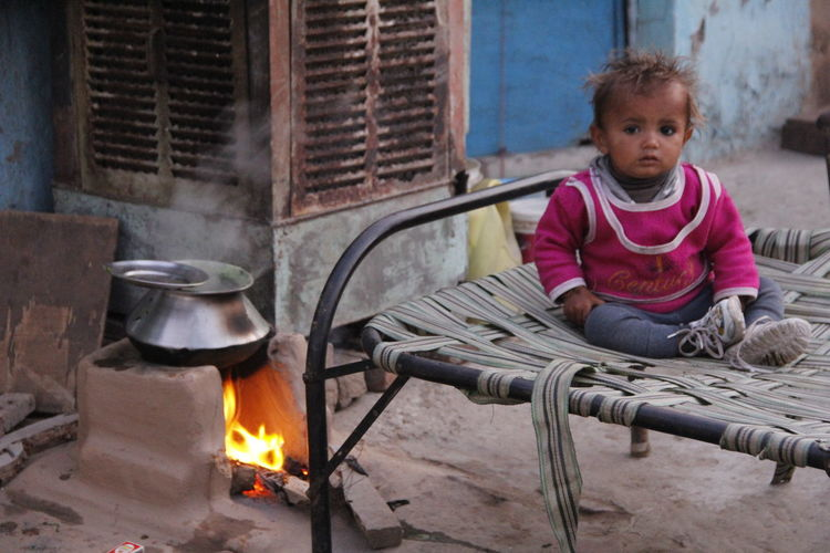 Close-up of boy sitting on cot by fireplace