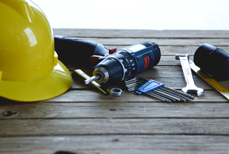 High angle view of work tools with hardhat on wooden table against white background