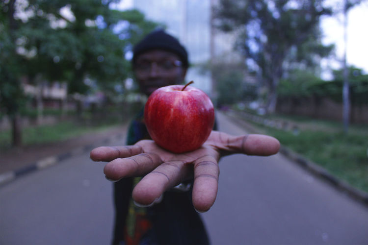 Man showing apple while standing on road