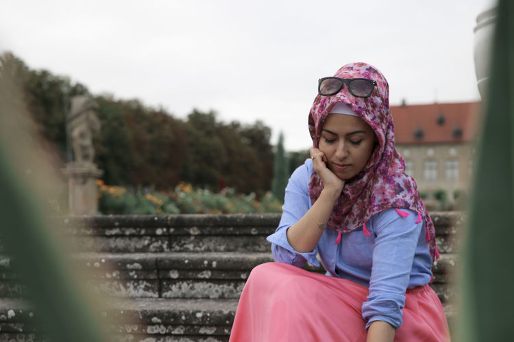 // beauty in Nature // Fashion Casual Clothing Child Clothing Contemplation Day Females Frame Front View Girls Hijab Innocence Leisure Activity Lifestyles Looking One Person Outdoors Portrait Real People Sitting Style Three Quarter Length Women Young Adult Young Women