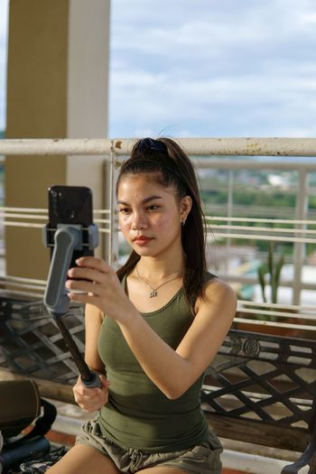 Portrait of young woman photographing while sitting on railing