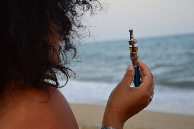 Close-Up Of Woman Holding Electronic Cigarette Against Sea