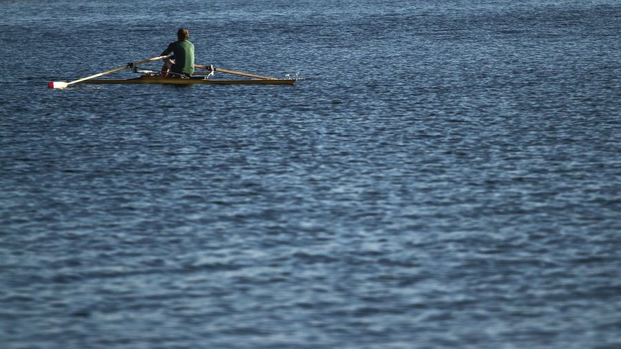 Rear view of man on rowing boat in lake