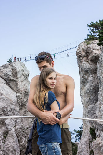 Portrait Of Shirtless Man Hugging Woman While Standing By Rock