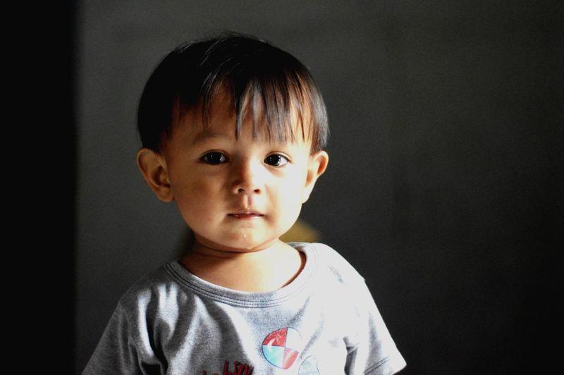 Portrait of cute boy against black background