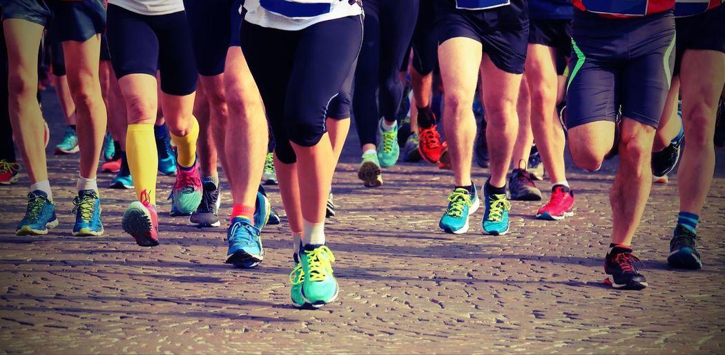 Low section of athletes running marathon on road