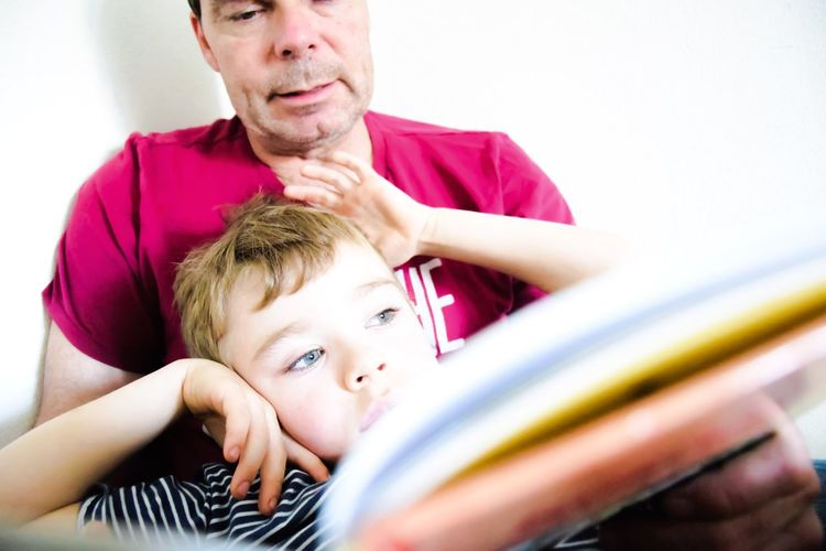Grandfather And Son Holding Book Against White Wall