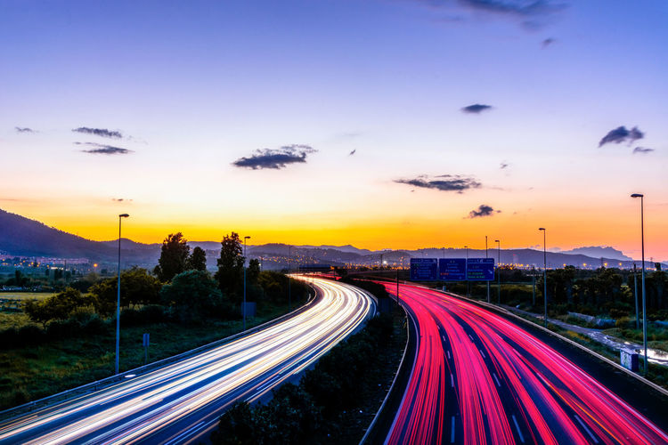 High angle view of light trails on highway at sunset