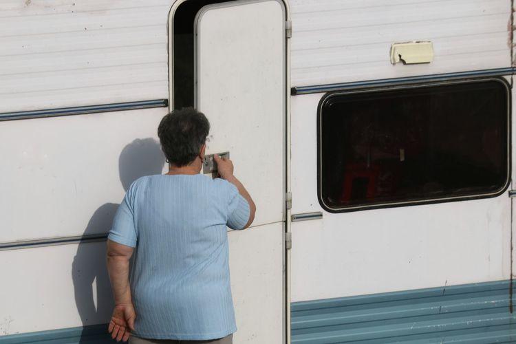 Rear view of woman opening door of camper trailer